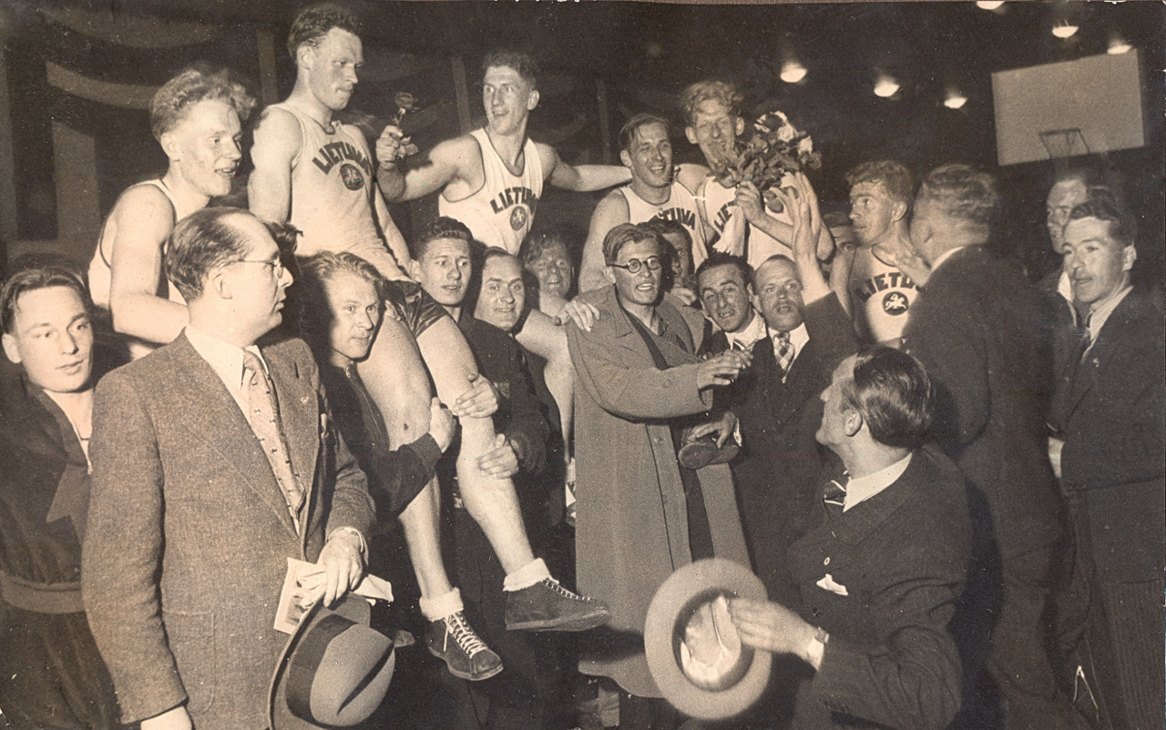Jaunā Eiropas basketbola čempionvienība – Lietuvas izlase – kopā ar līdzjutējiem 1937. g. 7. maijā Rīgā. Lietuviešu panākums pārsteidza Eiropas basketbola ekspertus. Tagad tie iepazina jauno Lietuvas izlases sastāvu, kurā nozīmīga loma bija ASV dzimušajiem lietuviešu izcelsmes basketbolistiem. Foto: Latvijas Sporta muzeja krājumā (autors nezināms).