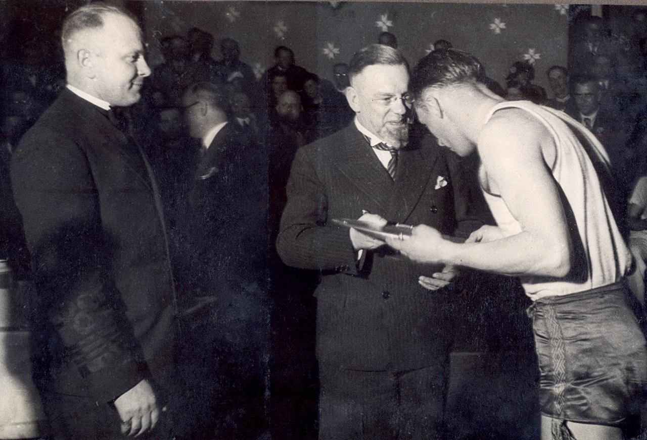 Meistaru jeb čempionu apbalvošana 1937. g. 7. maijā. Latvijas Fiziskās kultūras un sporta komitejas priekšsēdis un Latvijas Olimpiskās komitejas prezidents Marģers Skujenieks pasniedz galveno balvu – sudraba šķīvi – Lietuvas izlases pārstāvim.