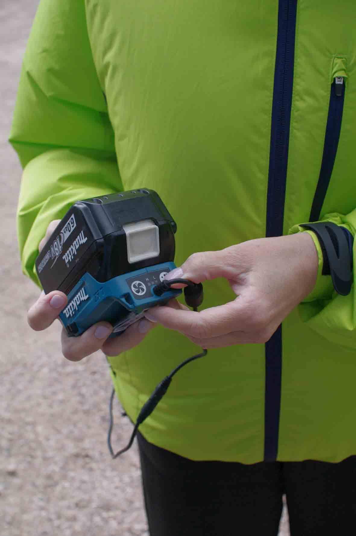Akumulators tiek pieslēgts caur speciālu adapteru, ko var ielikt kabatā vai piespraust pie jostas.