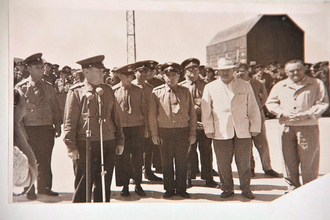 Pie mikrofona ģenerālis Vladimirs Putiļins, pa labi no viņa kosmonauts Valērijs Bikovskis, kosmonauts Andrijans Nikolajevs, valsts galva Ņikita Hruščovs un konstruktors Sergejs Koroļovs.