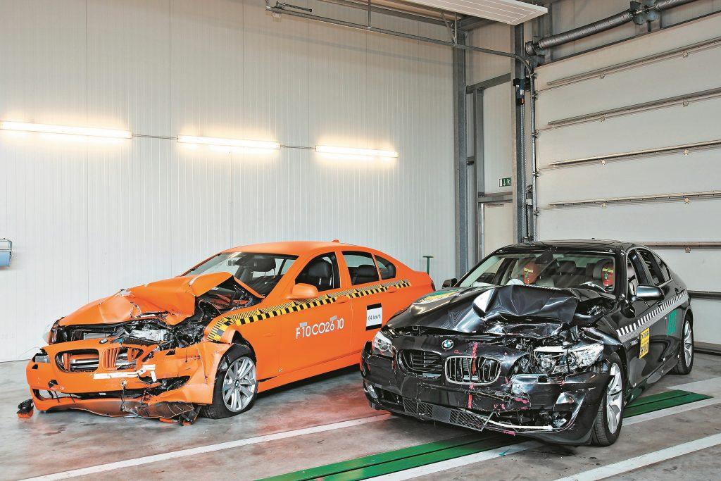 Oranžajā krāsā 5. serijas BMW bez brıdinajuma sistemas. Melnās krāsas BMW uzstādīta avārijas bremžu funkcija