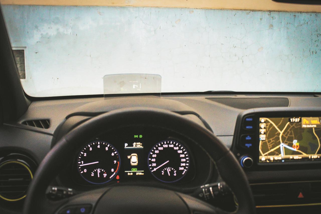 Mehāniskas skaņas pavadīts, no paneļa iznirst ekrāns, kurā redzams braukšanas ātrums un navigācijas norādes ar iespēju pieregulēt attēla pozīciju, asumu un pat slīpumu.