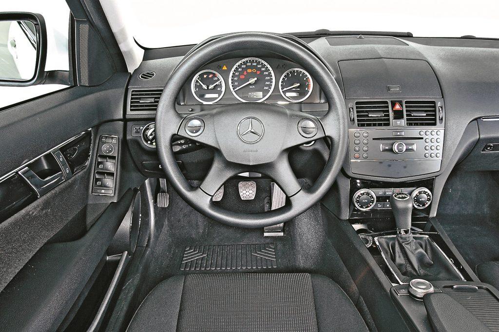 Mercedes bāzes modeļa salons: melns audums, vienkārša plastmasa, uz slēdžiem nav mīkstās lakas. Toties pārskatāmība laba: C klasē labi jutīsies visi