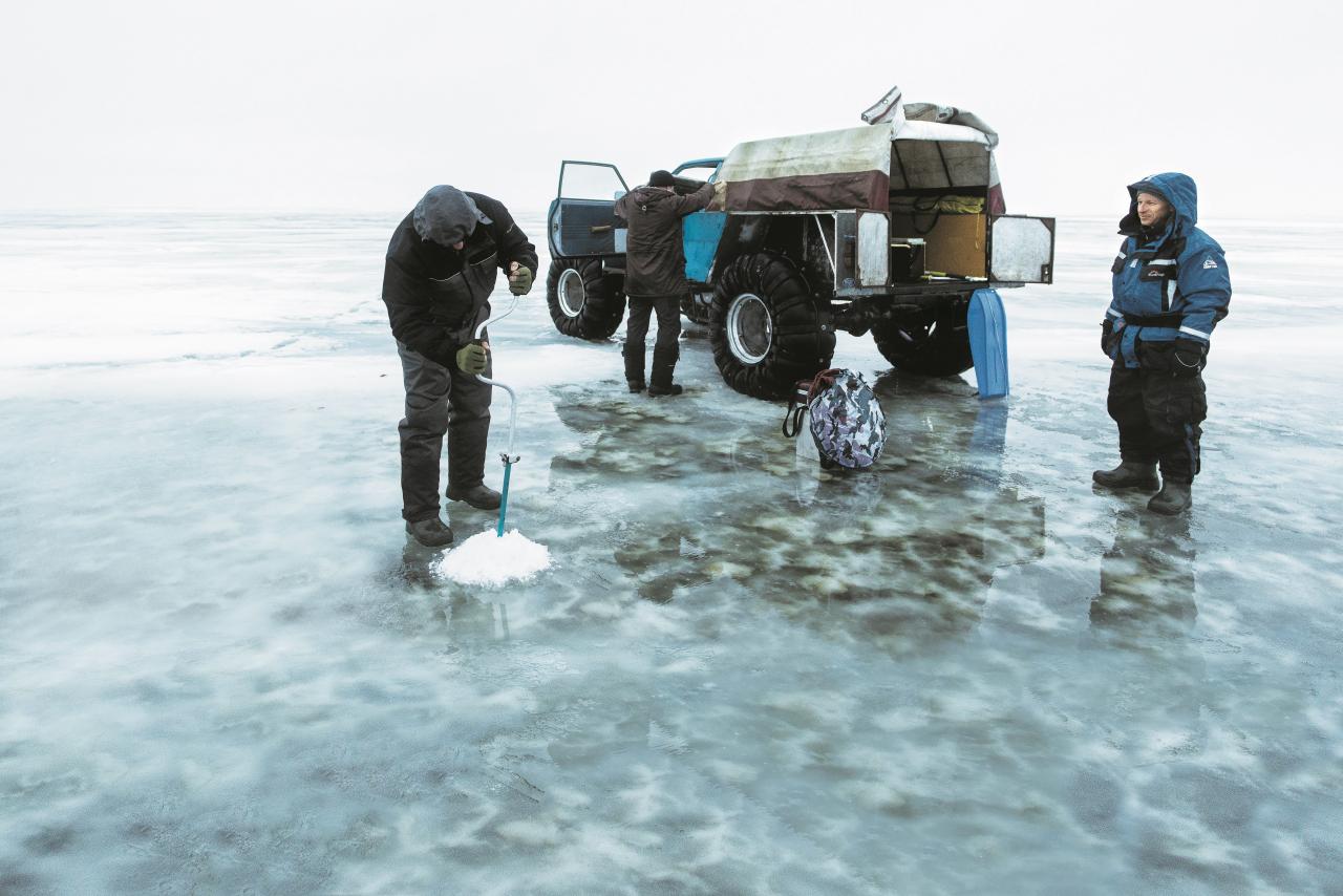 Divi kilometri līdz Krievijai: Aleksandrs Goidins (vidū) atbraucis pēc diviem makšķerniekiem uz ledus.