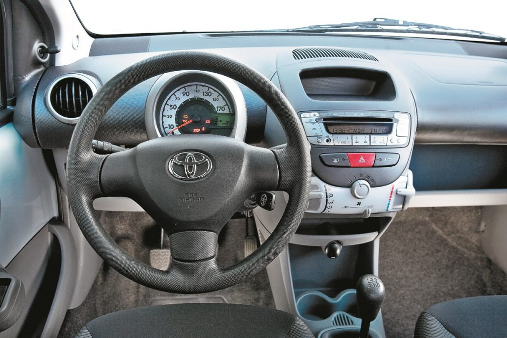 iPod paaudzes priekšējais panelis: Toyota Aygo trīs spieķu stūre ir ērta, tam ir neskaitāmas sīkumu novietnes un atsevišķa vadības vienība ar netiešu apgaismojumu apsildei un ventilācijai. Tas izskatās stilīgi.