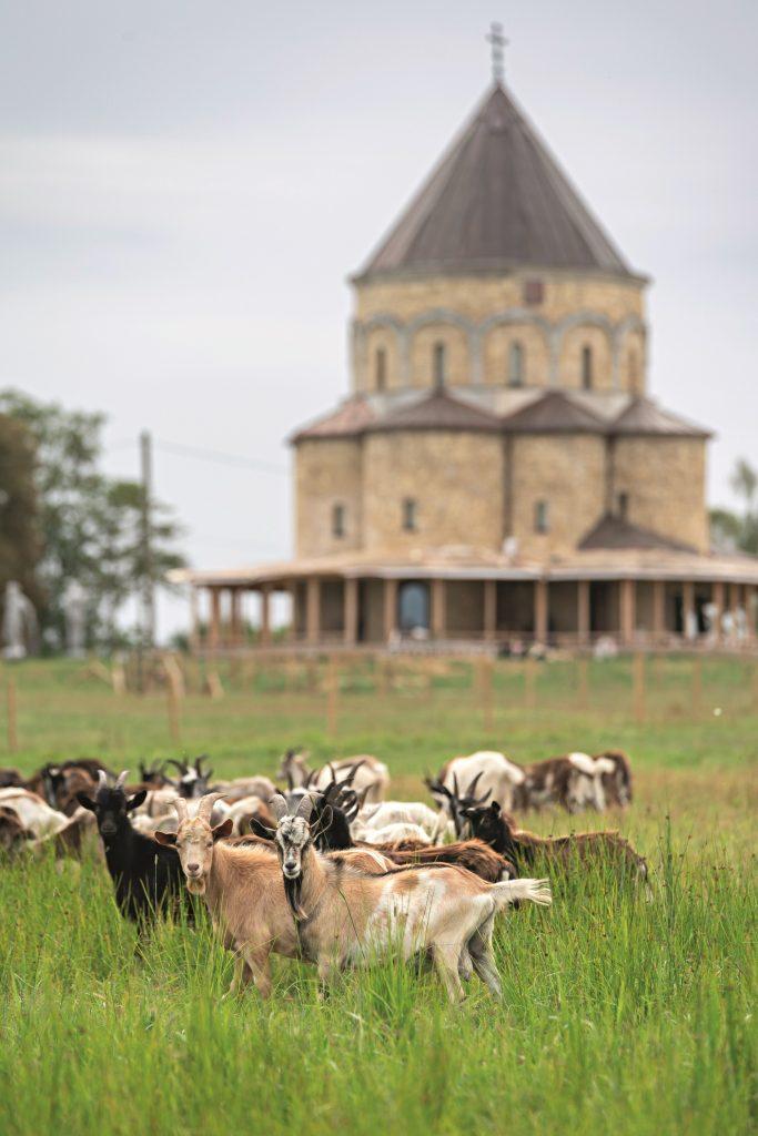 Ainava aiz loga– nesen uzceltā Bruknas Svēto apustuļu baznīca, kas ir Armēnijas senās Karsas katedrāles miniatūra kopija. Enriko tās celšanā pielicis roku. Arī laulāti viņi ar Annu ir te.