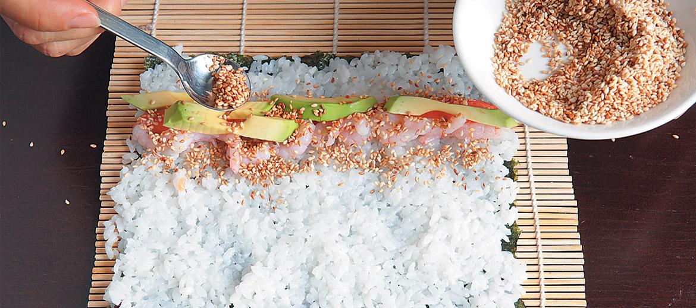 Rīsus uzklāj, atstājot nelielu brīvu maliņu. Tad apmēram 5 cm no malas liekpildījumu.Suši varpildītar lasi, garnelēm, avokado, pa virsu pārkaisītas grauzdētas sezama sēklas.