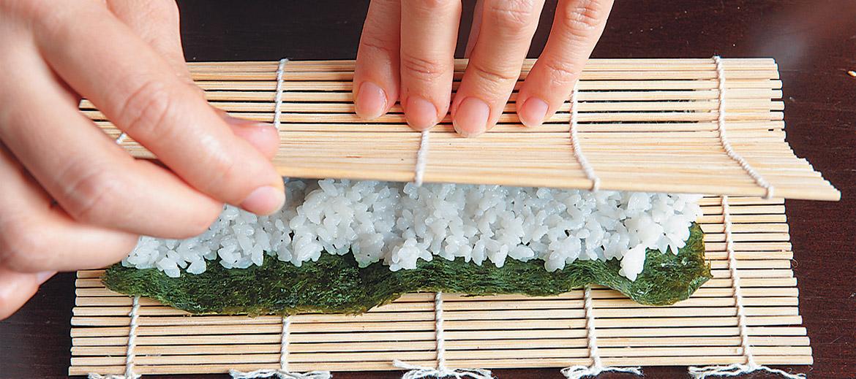 Paklājiņu paņem aiz priekšējās malas un kopā ar rīsiem un lapu pārklāj pāri pildījumam tā, lai pildījums būtu nosegts, un malu bez pildījuma uzmanīgi ieritina rullītī.