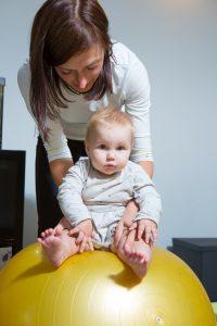 Labs vingrinājums, šūpojot bērnu uz bumbas. Tas izkustina un stabilizē iegurni, korsetes muskuļus, kā arī vingrina līdzsvara izjūtu, kas mazajam būs ļoti svarīga brīdī, kad viņš piecelsies kājās.