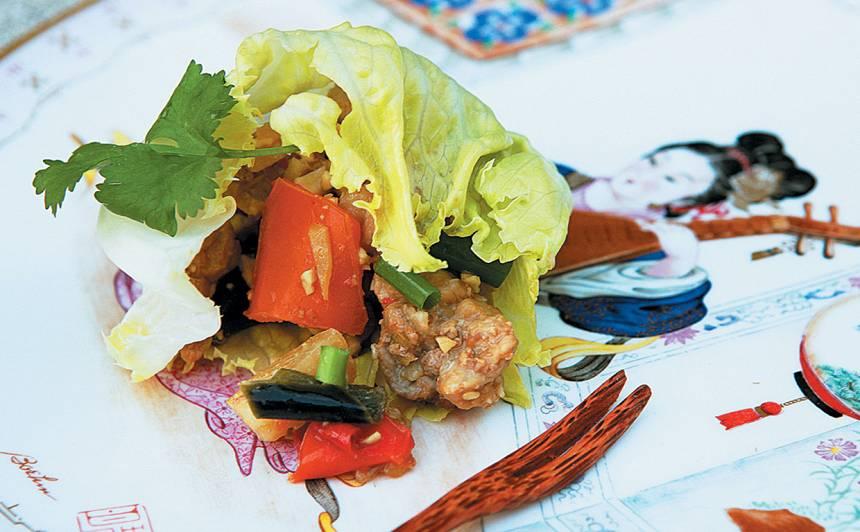 Cūkgaļas un dārzeņu sautējums, pasniegts salātlapā