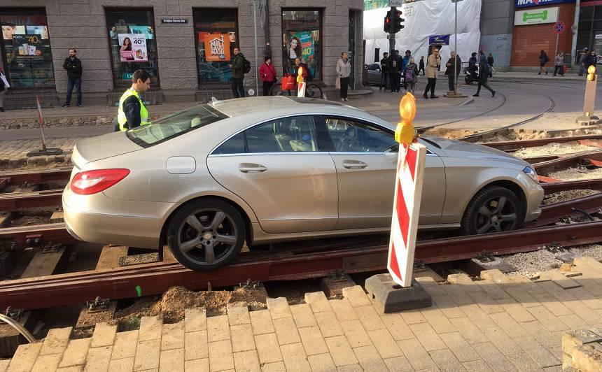VIDEO: Krišjāņa Barona ielā <strong><em>Mercedes-Benz</em> iekrīt bedrē</strong> un <em>uzkaras</em> uz sliedēm