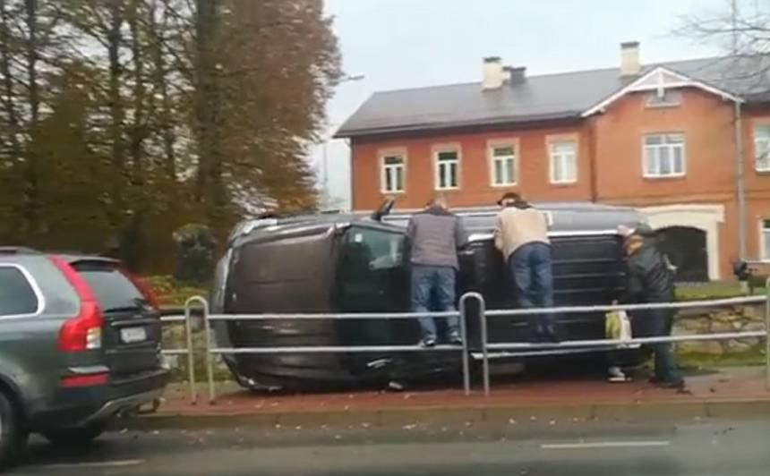 VIDEO: <strong>Valmierā dārgs apvidus auto uzlido uz ietves un apgāžas,</strong> cietušas divas personas