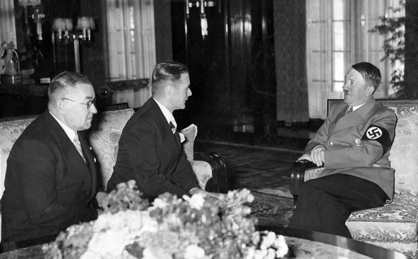 """Ārlietu ministrs Vilhelms Munters sarunājās ar Ādolfu Hitleru. Saruna, kas ilga 50 minūtes, notika Jaunā Reiha Valsts kancelejas ēkā pēc neuzbrukšanas pakta parakstīšanas. """"Hitlers mani pārsteidza ar savu samērā nelielo augumu un kautrīgumu (..) Viņš atzīmēja pakta noslēgšanu un teica, ka tas radīs noturīgu pamatu mūsu savstarpējās attiecībās,"""" vēlāk rakstījis Munters. Pa kreisi Latvijas sūtnis Vācijā Edgars Krieviņš. 1939. gada 7. jūnijs."""