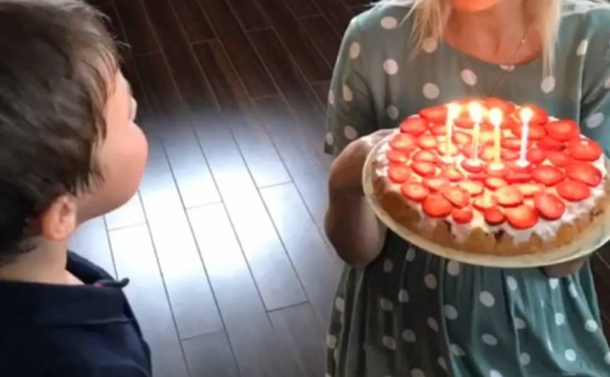 Māra Grigaļa sieva ZANE, kas šobrīd ir ģimenes trešā bērniņa gaidībās, pasniedz jubilejas torti četrgadīgajam MĀRCIM.