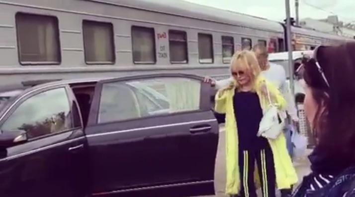 Ceļojumam Alla Pugačova izvēlējās sportiska stila apģērbu un trenci modīgā neona krāsā.