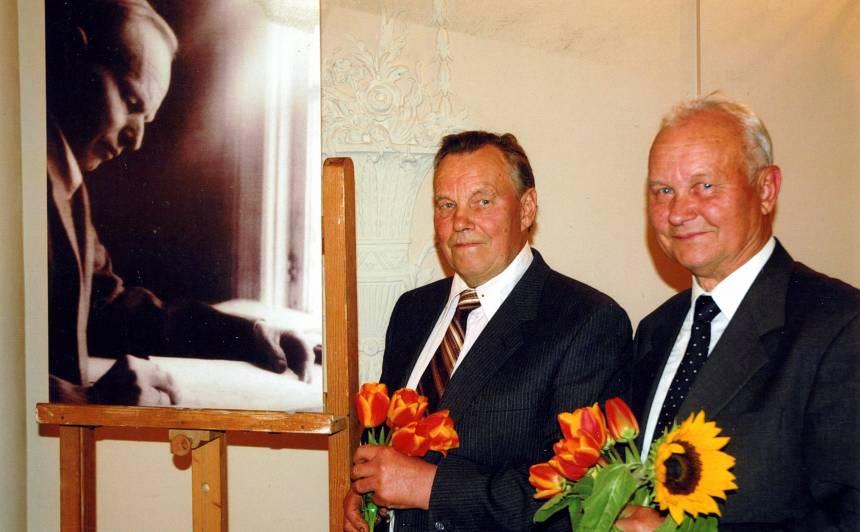 Dēli Māris un Juris pie tēva portreta viņa simtās jubilejas atceres pasākumā Ķekavā.